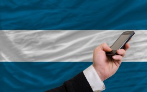 man holding cell phone in front national flag of el salvador symbolizing mobile communication and telecommunication
